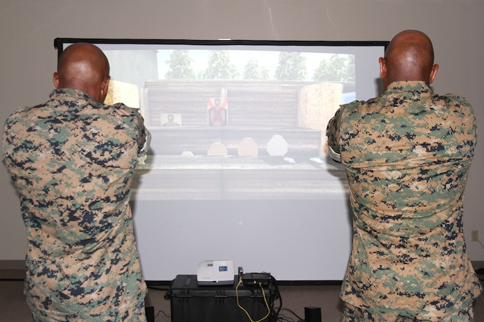 Marine Corps Logistics Base Albany Commanding Officer Col. Alphonso Trimble (right) and Sgt. Maj. Johnny Higdon (left) test out an active shooter simulator aboard Marine Corps Logistics Base Albany, August 8. Marine Corps Police Department recently purchased the simulator to test officers's ability to make decisions during intense situations. It also prepares officers for real-life scenarios such as traffic stops and active shooter events. (U.S. Marine Corps photo by Re-Essa Buckels)