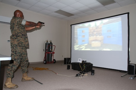 Marine Corps Logistics Base Albany Commanding Officer Col. Alphonso Trimble (right) test out an active shooter simulator aboard Marine Corps Logistics Base Albany, August 8. Marine Corps Police Department recently purchased the simulator to test officers' ability to make decisions during intense situations. It also prepares officers for real-life scenarios such as traffic stops and active shooter events. (U.S. Marine Corps photo by Re-Essa Buckels)