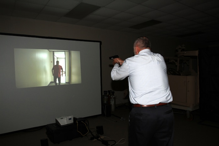 Kent Morrison, Executive Director, the Operations and Training Division, tests out an active shooter simulator aboard Marine Corps Logistics Base Albany, August 8. Marine Corps Police Department recently purchased the simulator to test officers's ability to make decisions during intense situations. It also prepares officers for real-life scenarios such as traffic stops and active shooter events. (U.S. Marine Corps photo by Re-Essa Buckels)