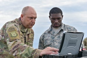 Master Sgt. Kyle Goins (left) and Airman First Class Keontay Curry, both communications specialists assigned to the Kentucky Air National Guard's 123rd Contingency Response Group, set up computer systems for Operation Huron Thunder at the Alpena Combat Readiness Training Center in Alpena, Mich., July 22, 2018. The 123rd CRG worked in conjunction with the U.S. Army's 690th Rapid Port Opening Element to operate a Joint Task Force-Port Opening during the exercise. The objective of the JTF-PO is to establish a complete air logistics hub and surface distribution network. (U.S. Air National Guard photo by Maj. Allison Stephens)