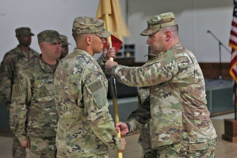 U.S. Army Capt. Filiberto Pacheco (left) and U.S. Army Col. Robert Kuth (right) conduct the exchange of the company colors during the Headquarters Company of Area Support Group Qatar's change of command at Camp As-Sayliyah, Qatar, July 31, 2018.  The exchange of the company colors symbolized Capt. Pacheco accepting command of the company.