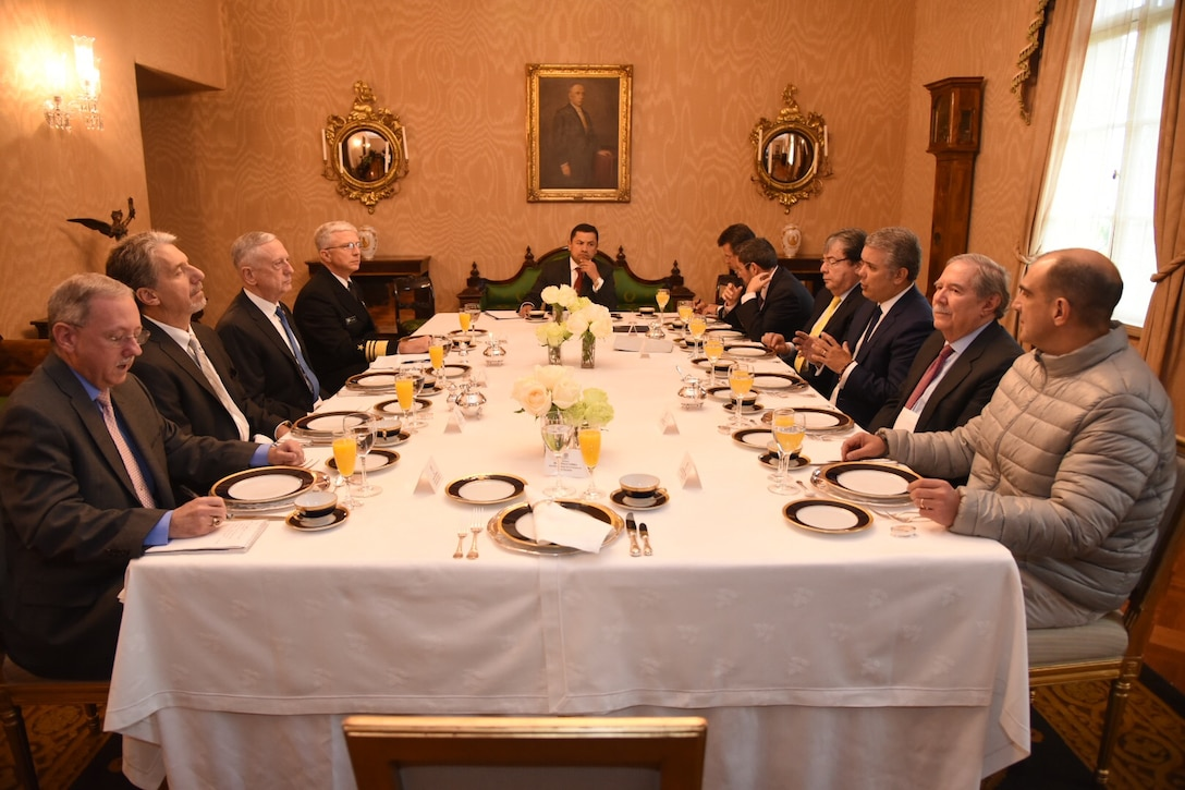 Colombia's president is flanked at a conference table by nine men, including Defense Secretary James N. Mattis.