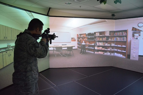 Tech. Sgt. Scott Buske, a spectral analysis section chief with the 21st Surveillance Squadron, Air Force Technical Applications Center, Patrick AFB, Fla., takes aim at a virtual active shooter using VirTra, a 300-degree wrap-around simulator used by members of the 45th Security Forces Squadron.  Buske and 17 members of his squadron spent a day with the law enforcement agents to learn more about how they protect the base. (U.S. Air Force photo by Susan A. Romano)