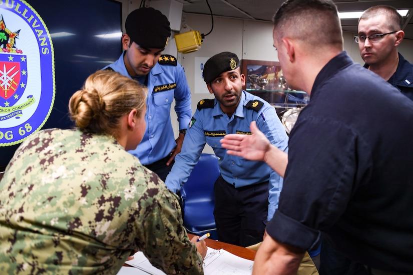 U.S. Navy and Coast Guard sailors discuss an exercise with Kuwaiti sailors.