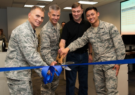 Col. Darren Buck, 310th Space Wing vice commander, Col. Stephen Slade, 310th Operations Group commander, Lt. Col. Timothy Gasmire (retired) and Airman 1st Class Reinhart Medina cut a ribbon during the reveal of an updated operations floor for the 6th Space Operations Squadron Aug. 4th, 2018.