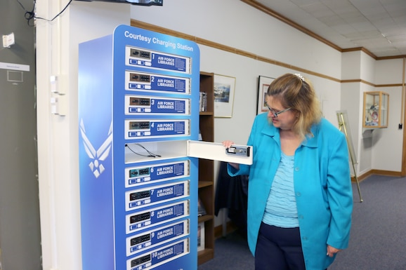 Jean Frantz, librarian at the AEDC Technical Library, demonstrates how to use the new charging station available at the library in Building 100 at Arnold Air Force Base. The charging station features 10 separate lockers with a variety of cords for different types of devices, such as phones and tablets. (U.S. Air Force photo by Deidre Ortiz)