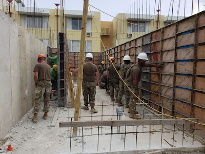 Soldiers help to build a house.