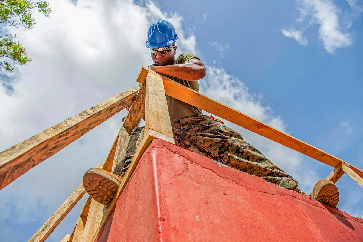 A Marine joins pieces of lumber together for the roof of a building.