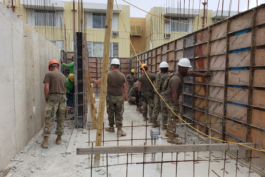 Soldiers work on construction site.