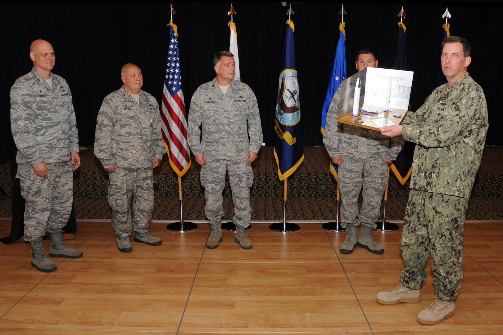 U.S. Navy Vice Admiral David M. Kriete, deputy commander of the U.S. Strategic Command (USSTRATCOM) present a trophy during a luncheon and ceremony at the Patriot Club on Offutt Air Force Base, Neb., Aug. 6, 2018. The 251st Cyberspace Engineering Installation Group, the 220th Engineering Installation Squadron, and the total force, United States Air Force engineering installation community were recognized for providing the infrastructure and cable installation for the new USSTRATCOM Command and Control facility over the past five years. (USSTRATCOM photo by Steve Cunningham)