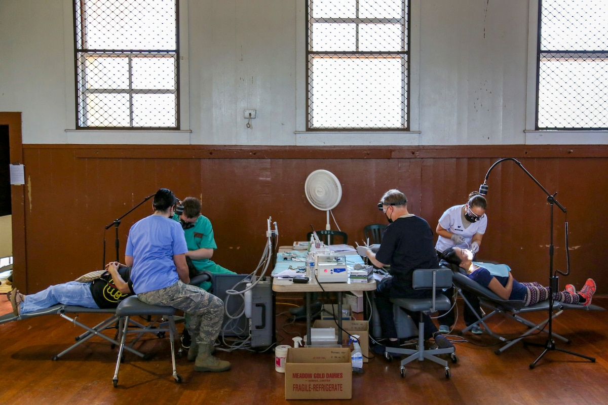 Service members provide dental care to patients in a big room.