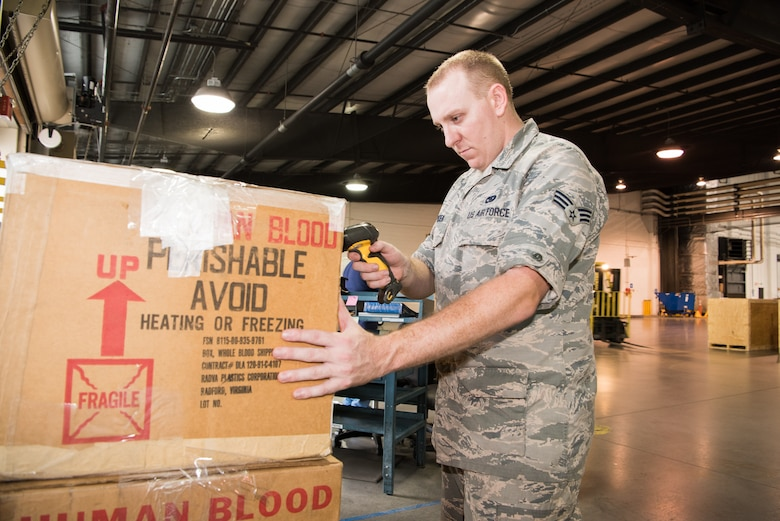Senior Airman Frank Houdek, 436th Aerial Port Squadron truck dock specialist, scans and processes a shipment of blood into the Global Air Transportation Execution System Aug. 2, 2018, at Dover Air Force Base, Del. Twice a week, Airmen at the truck dock stand by, ready to offload and process the blood shipments as soon as they arrive.