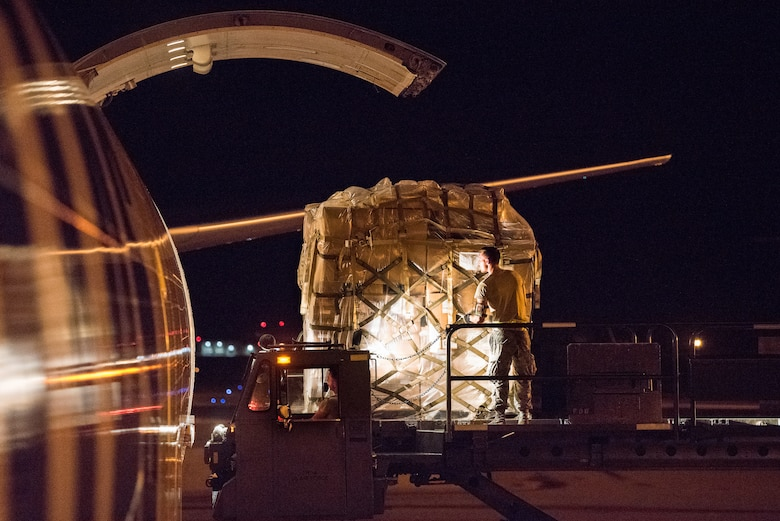 Team Dover Airmen with the 436th Aerial Port Squadron load pallets onto a commercial cargo aircraft Aug. 2, 2018, at Dover Air Force Base, Del. Blood shipments arrive via truck from the Armed Services Whole Blood Processing Laboratory East at Joint Base McGuire-Dix-Lakehurst and are typically airborne on an aircraft within two to six hours.