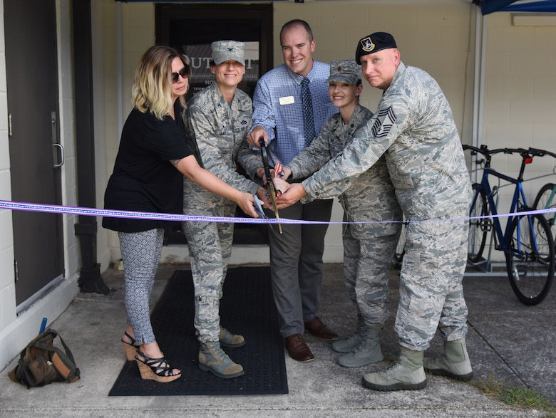 U.S. Air Force Col. Marcia Quigley, 81st Mission Support Group commander, and members of the 81st Force Support Squadron participate in a ribbon cutting ceremony during The Outpost grand opening at the Vandenberg Commons at Keesler Air Force Base, Mississippi, Aug. 17, 2018. The Outpost is a satellite store from the Outdoor Recreation Center with recreation items available for Airmen in the 81st Training Group. (U.S. Air Force photo by Kemberly Groue)