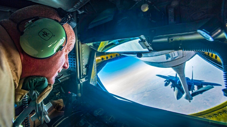 An airman watches an F-15 Eagle through a plane window during refueling.