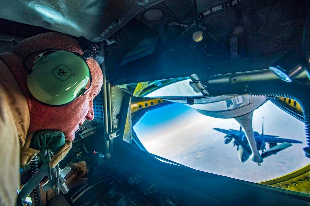 An airman watches an F-15 Eagle through a plane window during refueling.