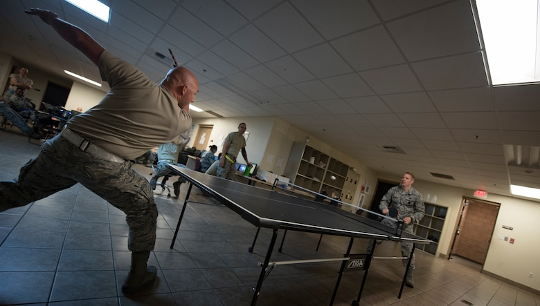 Staff Sgt. Joseph Johnson, 57th Aircraft Maintenance Squadron Lightning Aircraft Maintenance Unit avionics technician, plays table tennis with Staff Sgt. Joshua Harris, 57th AMXS Lightning AMU activity security manager, between shift changes at Nellis Air Force Base, Nevada, July 23, 2018. Airmen usually get time to unwind toward the end of their shift if their tasks are done for the day. (U.S. Air Force photo by Airman 1st Class Andrew D. Sarver)