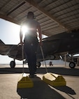 Senior Airman Dustin Hilton, 57th Aircraft Maintenance Squadron Lightning Aircraft Maintenance Unit crew chief, drags a set of chocks to an F-35A Lightning II fighter jet at Nellis Air Force Base, Nevada, July 23, 2018. Placing chocks under the tires of an aircraft prevents it from moving until the pilot is ready to taxi the aircraft to the runway. (U.S. Air Force photo by Airman 1st Class Andrew D. Sarver)