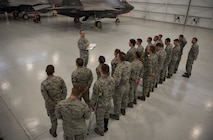 Airmen assigned to the 57th Aircraft Maintenance Squadron Lightning Aircraft Maintenance Unit line up in formation for roll call at Nellis Air Force Base, Nevada, July 24, 2018. Airmen must attend roll call to get the task list for their shift. (U.S. Air Force photo by Airman 1st Class Andrew D. Sarver)