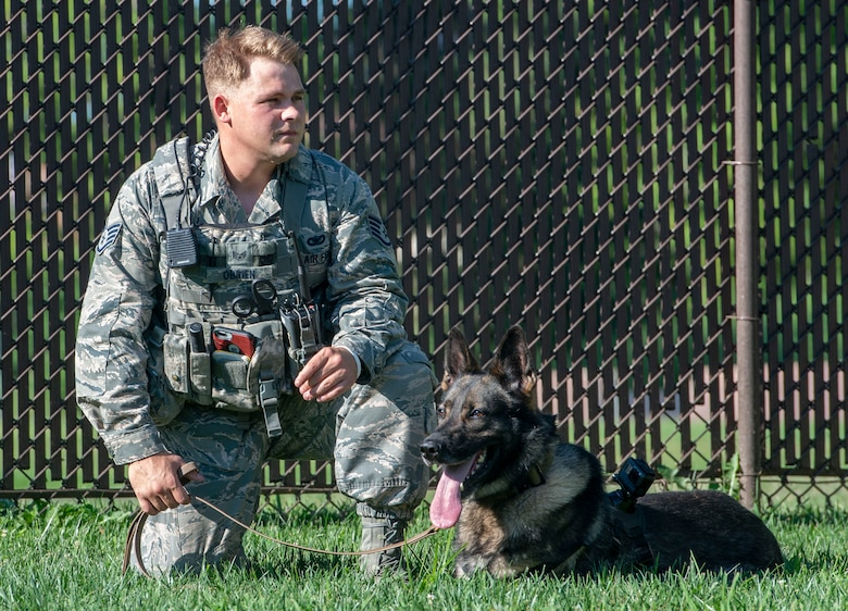 Staff Sgt. Christopher O'Brien, 375th Security Forces Squadron K-9 handler sits with his Military Working Dog, Irk, at the 375th SFS kennel  July 25, 2018.