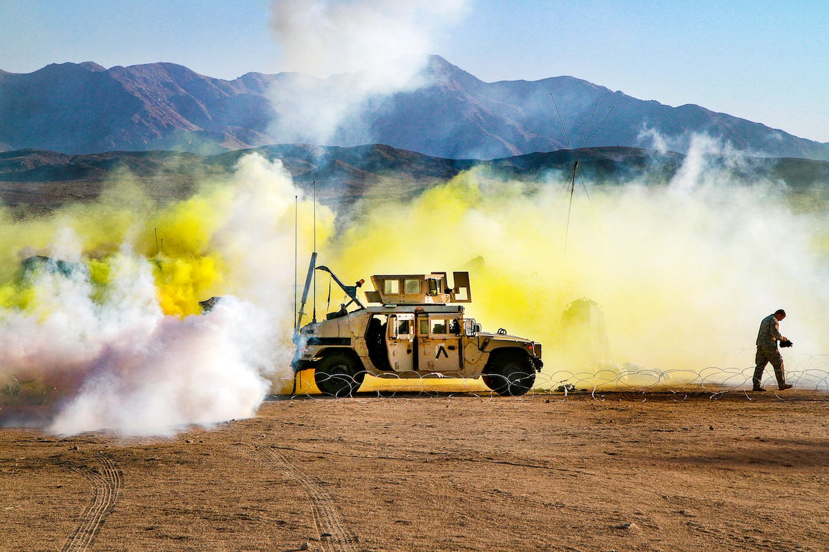 Yellow gas billows around a Humvee as a soldier walks away from the area.