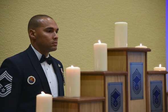 U.S. Air Force Chief Master Sgt. Rodney Deese, II, Mathies NCO Academy commandant, participates in the candle lighting ceremony during the Senior NCO Induction Ceremony at the Bay Breeze Event Center at Keesler Air Force Base, Mississippi, Aug. 17, 2018. More than 50 inductees were recognized during the event. (U.S. Air Force photo by Kemberly Groue)