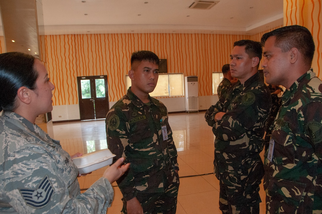 Tech. Sgt. Franchesa Pau'u, 169th Air Defense Squadron weapons controller talks with a group of Philippine Air Force airmen