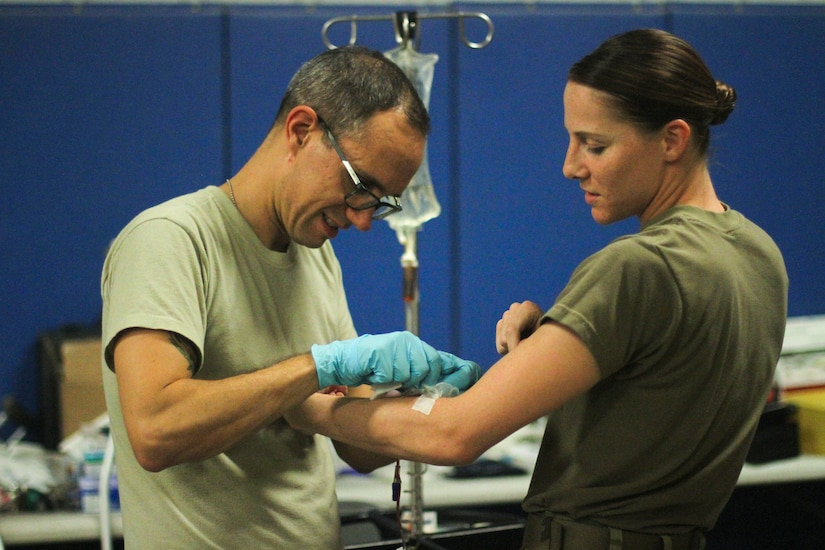 Medic removes IV from patient's arm.