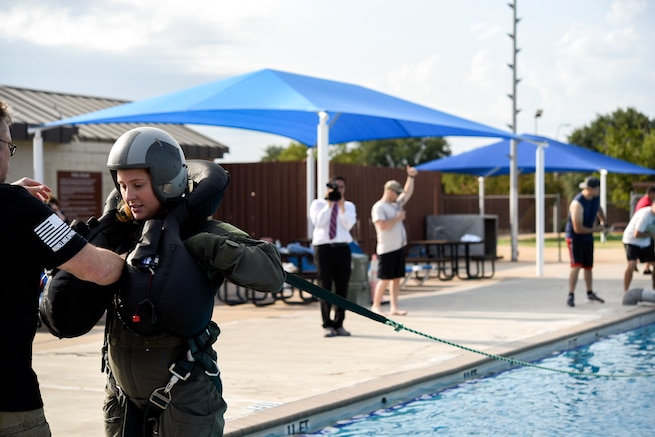 An airman is helped with putting her gear on, before she is pulled by a rope and drug through a pool as part of a training exercise.