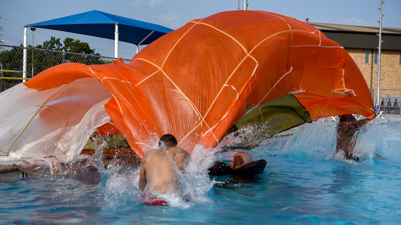 Two airman jump over a swimming pilot as they drape a parachute over her as part of the second scenario in the Water Survival Emergency Training.