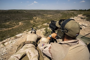 Sniper team fires at long-range targets.
