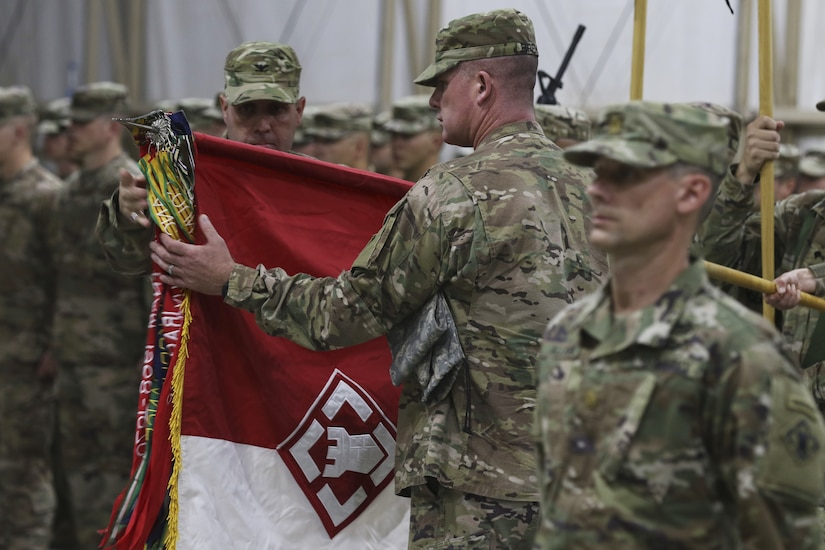 Col. Patrick Sullivan (facing camera) and Command Sgt. Maj. John Brennan, 20th Engineer Brigade commander and command sergeant major, respectively, unfurl their brigade's colors during a transfer of authority ceremony Aug. 16, 2018. The 20th, a XVIII Airborne Corps unit, took over the Task Force Spartan engineer brigade mission from the outgoing unit, the 35th Engineer Brigade, Missouri Army National Guard.