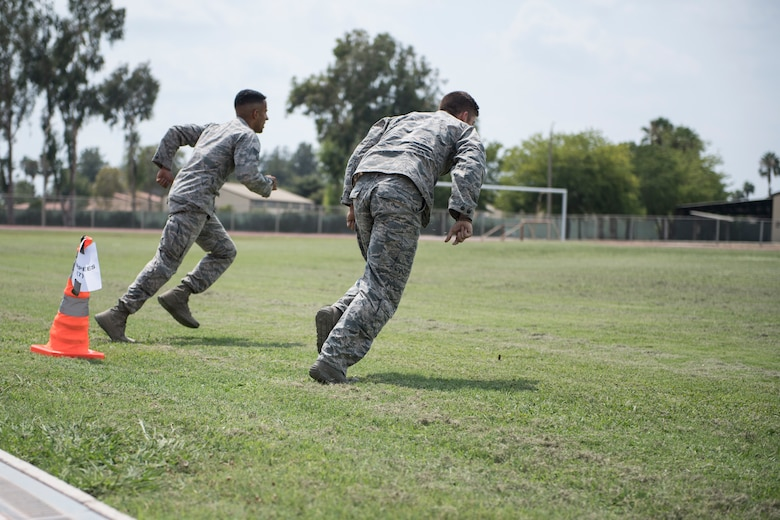 Airmen run to the next obstacle during an obstacle course.