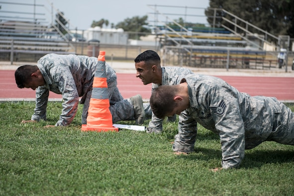 Airmen perform an obstacle during an obstacle course.
