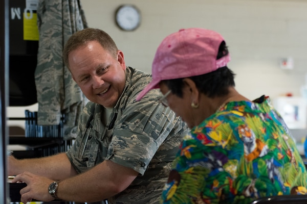 U.S. Air Force Col. William Bray, the commander of the 181st Medical Group, 181st Intelligence Wing of the Indiana Air National Guard, speaks to a community member during a physical screening at the Mitchell Pauole Community Center in Molokai, Hi., Aug. 13, 2018.