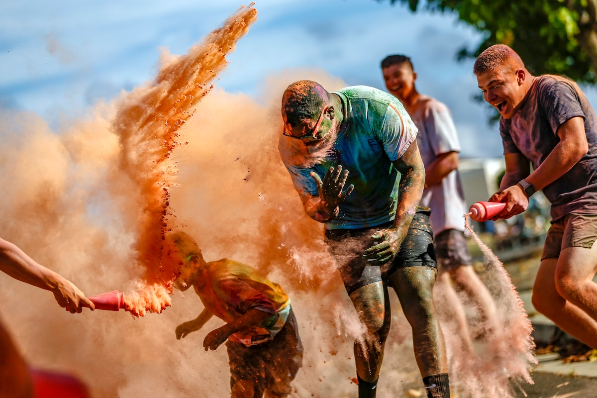Color run participants run through clouds of colored powder.
