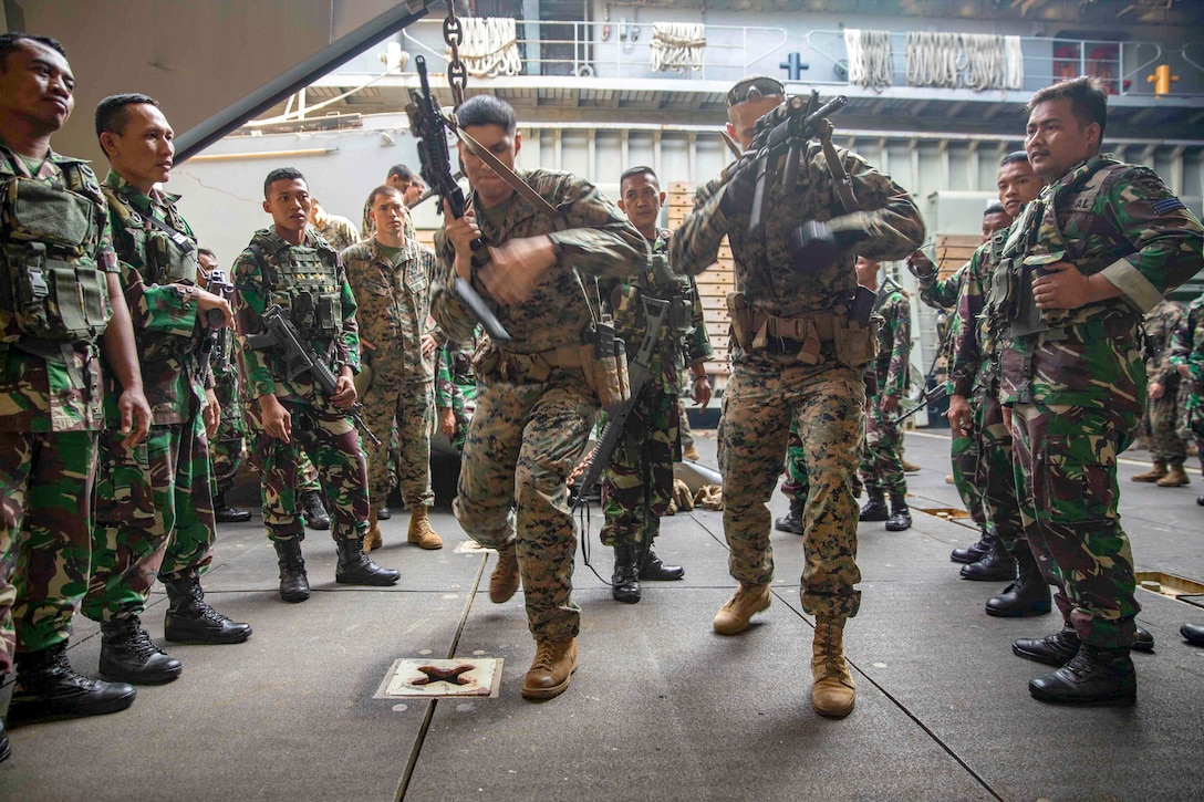 Marines demonstrate how to quickly reload their weapons.