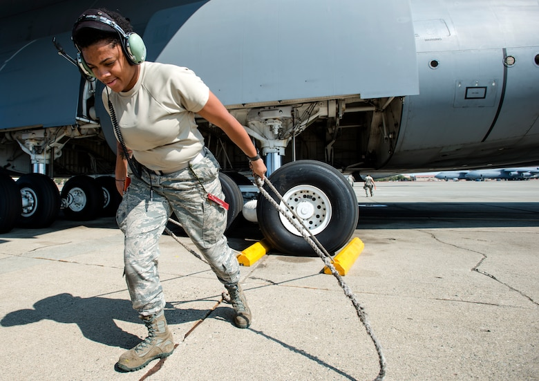 Airman 1st Class Amber St. Julian, 60th Aircraft Maintenance Squadron crew chief, removes chalks from the wheels of a C-5M Super Galaxy prior to launch on Aug. 11, 2018, at Travis Air Force Base, Calif. The 349th and 60th AMXS work together to launch aircraft in a seamless active duty and Air Force Reserve integration.