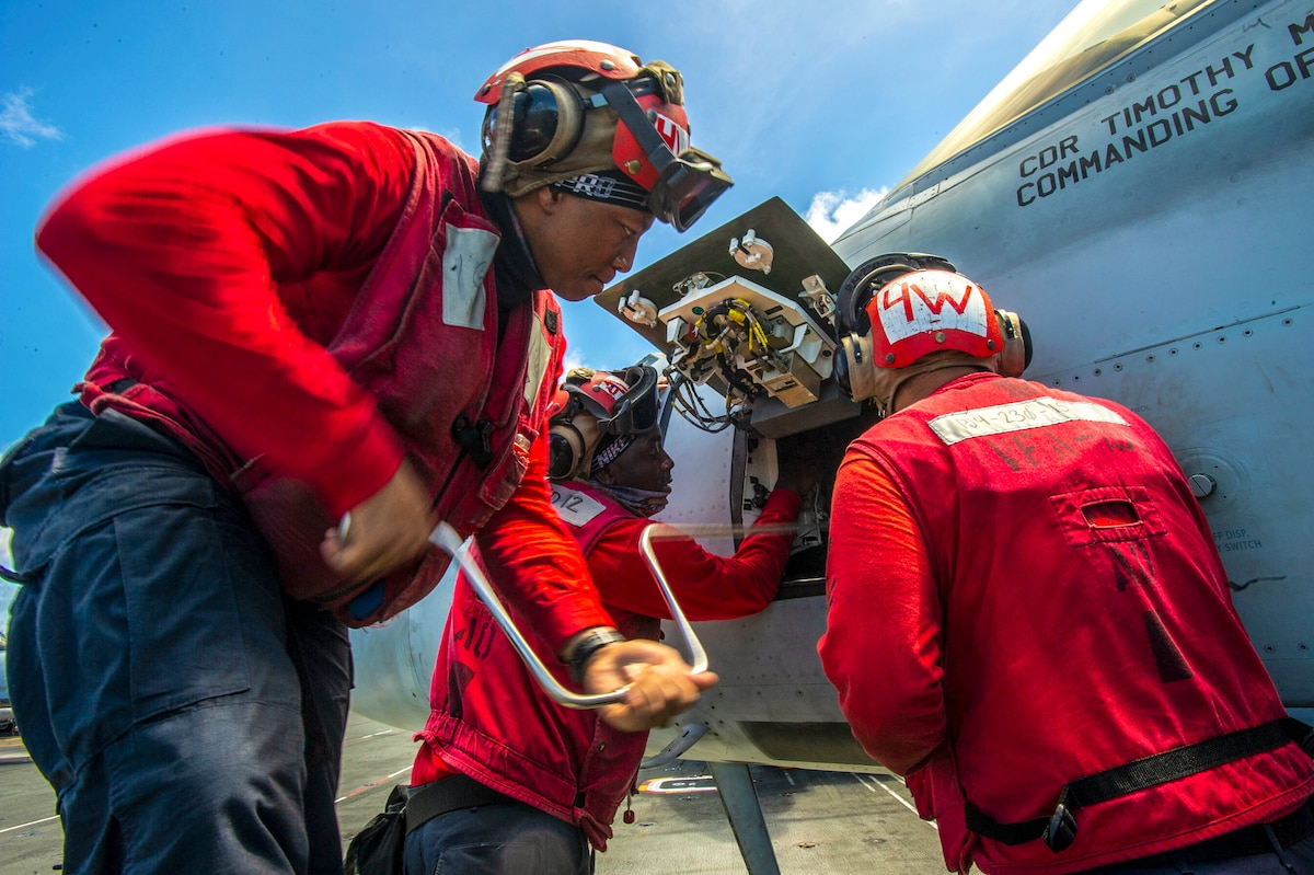 Three sailors, wearing red, use tools to work on an aircraft panel.