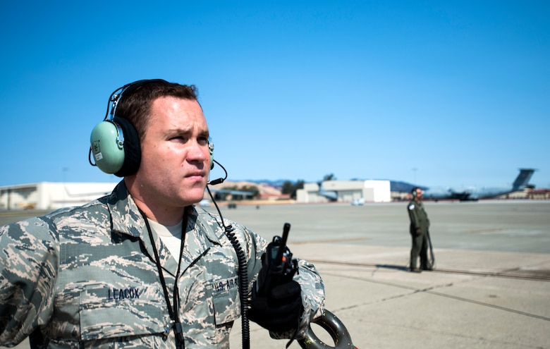Staff Sgt. Taylor Leacox, 349th Aircraft Maintenance Squadron crew chief, listens to his radio to ensure a C-5M Super Galaxy is cleared to launch on Aug. 11, 2018, at Travis Air Force Base, Calif. The 349th and 60th AMXS work together to launch aircraft in a seemless active duty and Air Force Reserve integration.