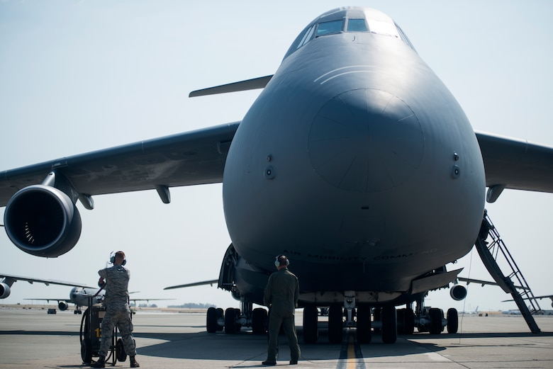 Crew chiefs for the 349th and 60th Aircraft Maintenance Squadrons stand by as the final checks on a C-5M Super Galaxy are completed prior to its launch on Aug. 11, 2018, at Travis Air Force Base, Calif. The 349th and 60th AMXS work together to launch aircraft in a seemless active duty and Air Force Reserve integration.