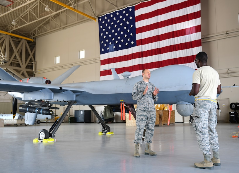 Chaplain Matthew, 432nd Wing/432nd Air Expeditionary Wing chaplain, speaks with Senior Airman Devin, 432nd Aircraft Maintenance Squadron avionics specialist, in the work center August 10, 2018, at Creech Air Force Base, Nev. Matthew spent 22 years in the U.S. Army as an infantryman, honor guardsman, and Apache helicopter pilot prior to becoming a U.S. Air Force Chaplain. He now leverages his combat experience to further help combat Airmen. (U.S. Air Force photo by Senior Airman Christian Clausen)