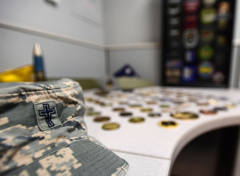 Chaplain Matthew's hat sits alongside his military coins and patches accumulated from 22 years in the U.S. Army as an infantryman, honor guardsman, and Apache helicopter pilot prior to becoming a U.S. Air Force Chaplain. He now leverages his combat experience to further help combat Airmen at Creech Air Force Base, Nev. (U.S. Air Force photo by Senior Airman Christian Clausen)