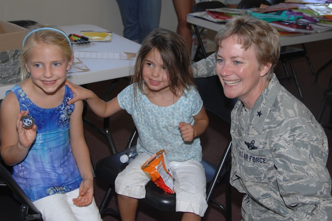 The challenge coin is a military tradition, and one Brig. Gen. Maryanne Miller has extended to the children of the 349th Air Mobility Wing Airmen she commands. During the wing's first Yellow Ribbon Reintegration Program conference, hosted by the 349th Maintenance Group, she visited with the children and presented coins to all of them. Other events for the YRRP included briefings, booths and prizes for parents, games, goodies and pizza for the kids, and finished with a spaghetti dinner and town hall meeting. The YRRP is DOD sanctioned, and provides assistance and support to deployers families pre-, during and post-deployment. (U.S. Air Force photo by Senior Master Sgt. Ellen L. Hatfield)