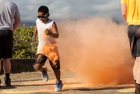 A race participant runs through colored powder during a 5K Color Dash race aboard Marine Corps Base Hawaii, Aug. 18, 2018. U.S. Marines with 1st Battalion, 3rd Marine Regiment, held a 5K Color Dash where volunteers showered racers with colored powder while also giving participants a scenic route near Fort Hase Beach. The race was a public event open to all U.S. service members, their families and members of the community to help raise funds for the battalion's ball. (U.S. Marine Corps photo by Sgt. Jesus Sepulveda Torres)