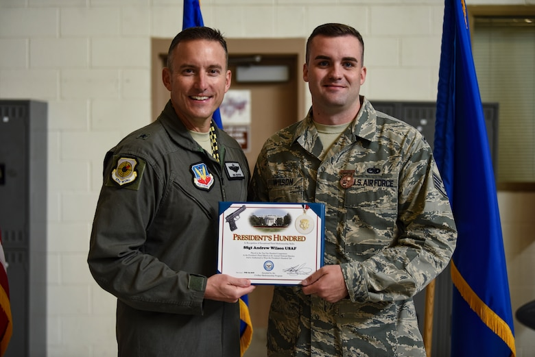 Brig. Gen. Robert G. Novotny, 57th Wing commander, presents the President's Hundred award to Staff Sgt. Andrew Wilson, 757th Aircraft Maintenance Squadron Strike Aircraft Maintenance Unit F-15E Strike Eagle fighter jet crew chief, at Nellis Air Force Base, Nevada, Aug. 15, 2018. Wilson earned the President's Hundred tab after shooting a perfect score at the 2018 National Trophy Pistol Matches and Small Arms Firing School at Camp Perry, Ohio. (U.S. Air Force photo by Airman 1st Class Andrew D. Sarver)