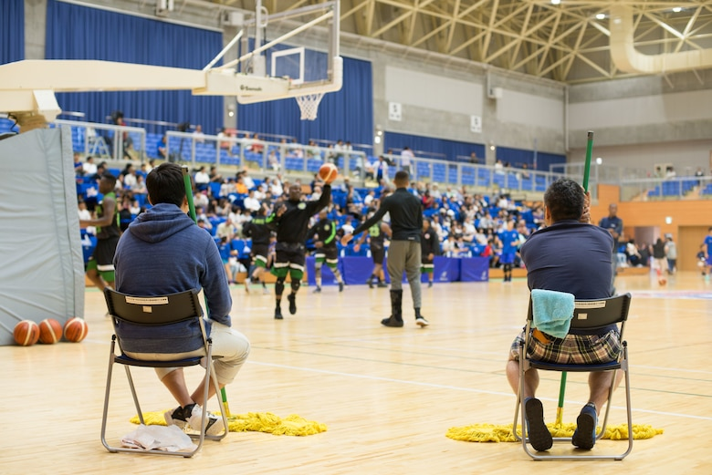 Sweepers sit ready to wipe the floor clean during the Aomori Wat's and Misawa Jets exhibition game at the Misawa International Sports Center in Misawa City, Japan, Aug. 18, 2018. The sweepers ran out at every timeout, foul, referee break and period intermission keeping the floor clean of sweat, tears and sometimes blood. The game's organizers sought to improve U.S.-Japan relations while fostering positive community engagement with Misawa Air Base's host nation neighbors. (U.S. Air Force photo by Tech. Sgt. Benjamin W. Stratton)