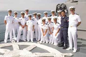 A group of ROTC midshipmen pose for a photo on board a ship.