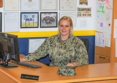 Navy Petty Officer 1st Class Caroline Ballad, a recruiter, works at her desk processing future sailor's paperwork for entering the Navy at Navy Talent Acquisition Group Rocky Mountain-Utah Division, Taylorsville, Utah, Aug. 10, 2018. Navy photo by Petty Officer 3rd Class Zachary S. Eshleman