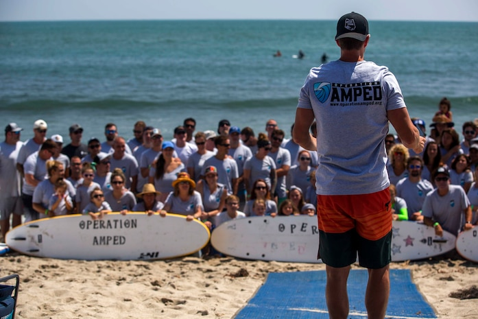 Recovering service members, veterans, volunteers and their loved ones prepare for a group photo during the 12th Annual Operation Amped Surf Camp at San Onofre Beach at Marine Corps Base Camp Pendleton, California, Aug. 18, 2018. Operation Amped is a nonprofit organization that supports wounded, ill and injured service members and veterans throughout their recovery.